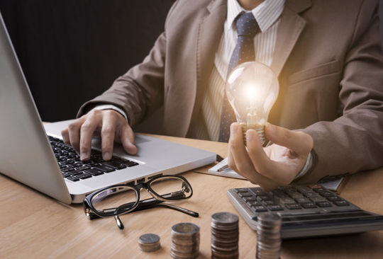 Business man hand holding lightbulb with using calculator to calculate. concept idea saving finance.