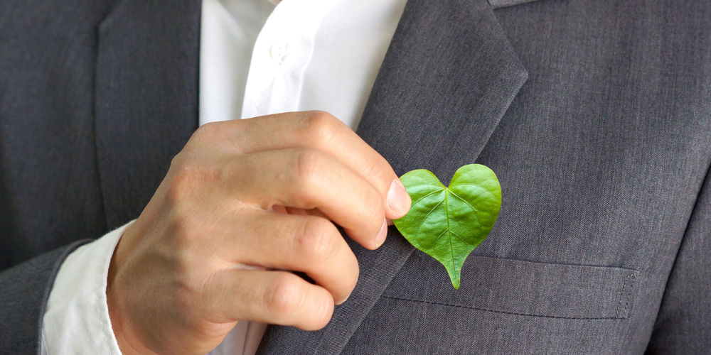 leaf over business suit pocket implying corporate social responsibility